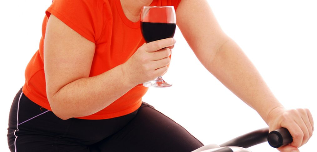 Woman on stationary bike with a glass of red wine