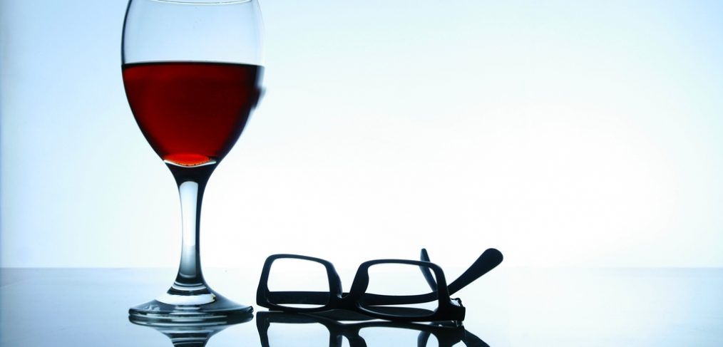 Glass of red wine and eye glasses