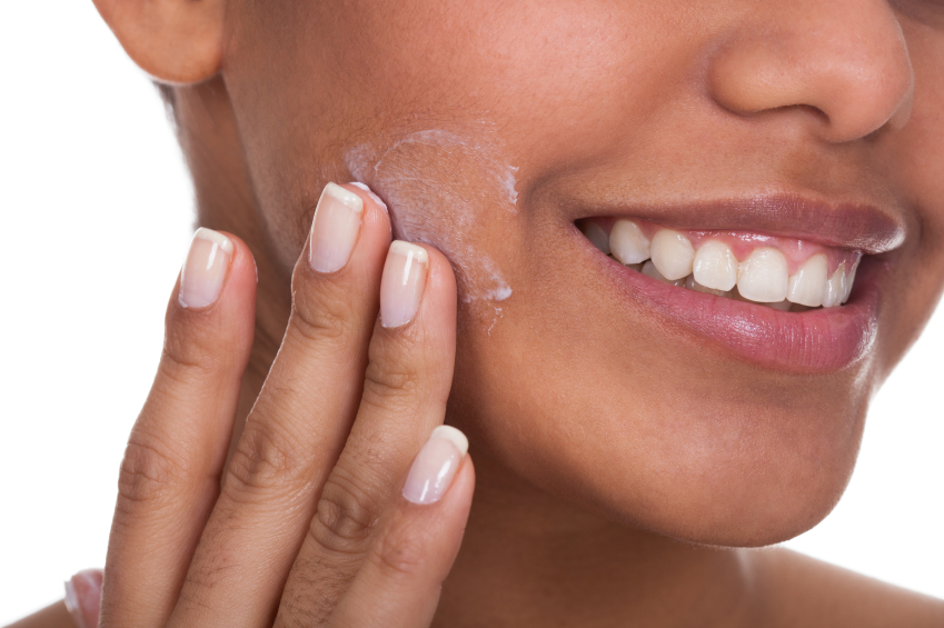 Young Woman Applying Cream On Her Face Over White Background