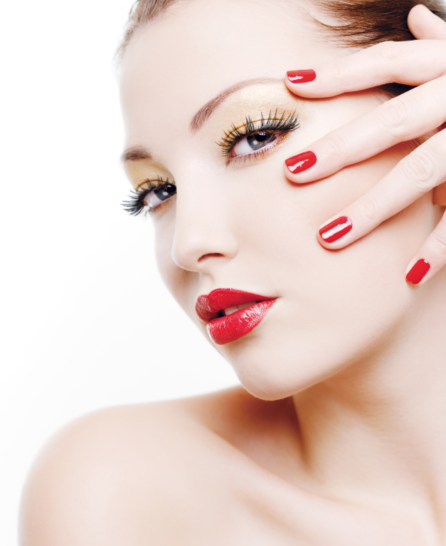 Woman with seasonal makeup colors like shimmer eye makeup and red lips and nails