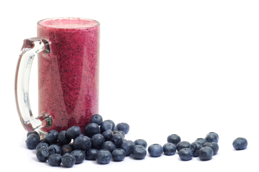 Large glass cup filled with a blueberry smoothie and surrounded by blueberries