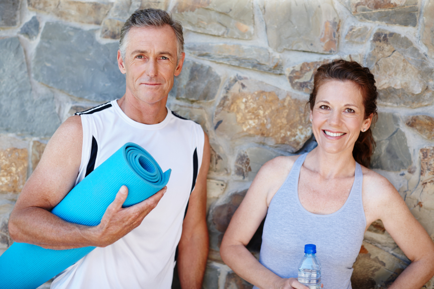 A mature couple holding their yoga gear outside with broad smiles