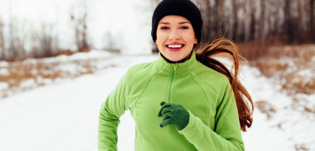 Happy young woman exercising in winter