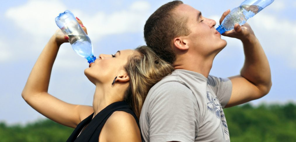 Couple drinking water outside