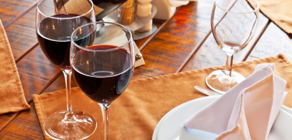 Cabernet filled wine glasses near food plates