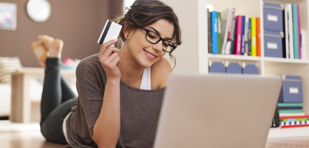 Woman with credit card in front of laptop