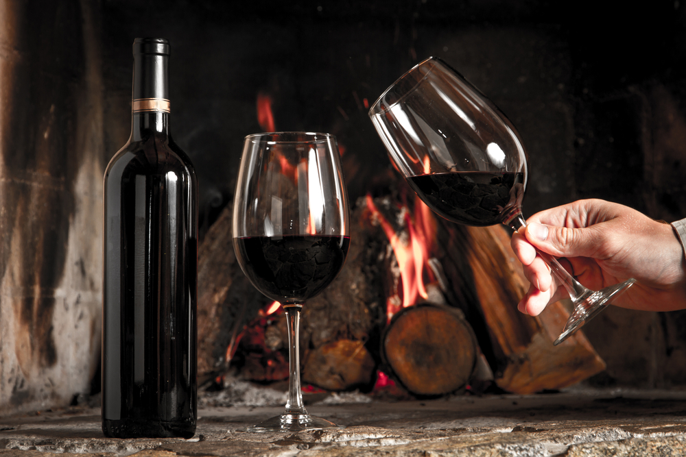 Glasses of wine by the fireplace.