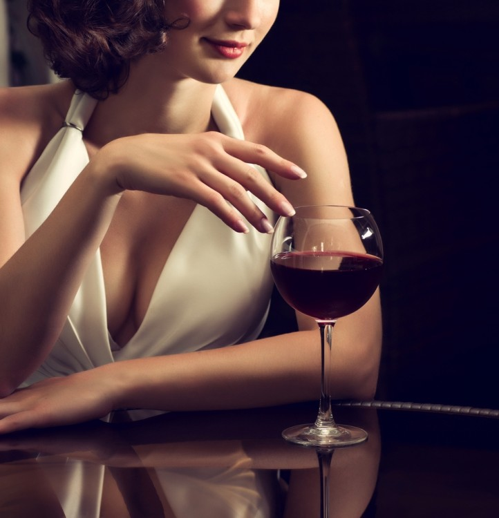 Woman in white holding a glass of red wine.