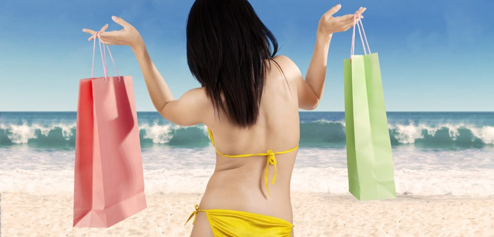 Rear view of woman in swimsuit holding shopping bags.