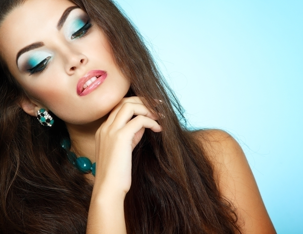 Woman with electric blue makeup on her eyes.