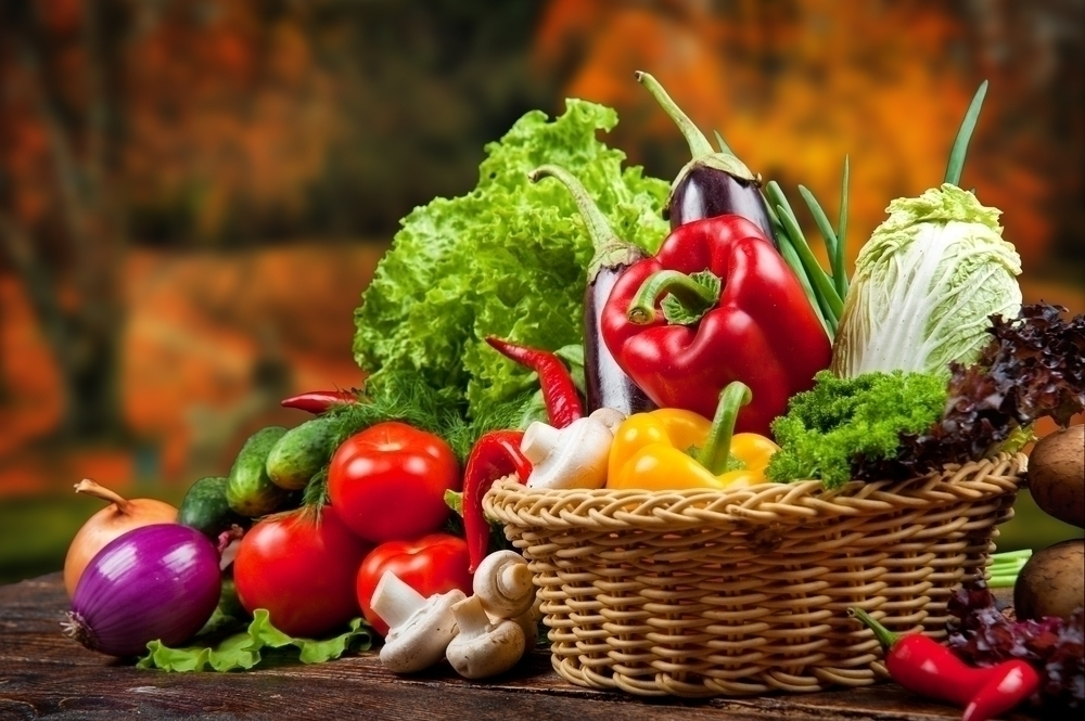 Fresh vegetables overflowing from a basket.
