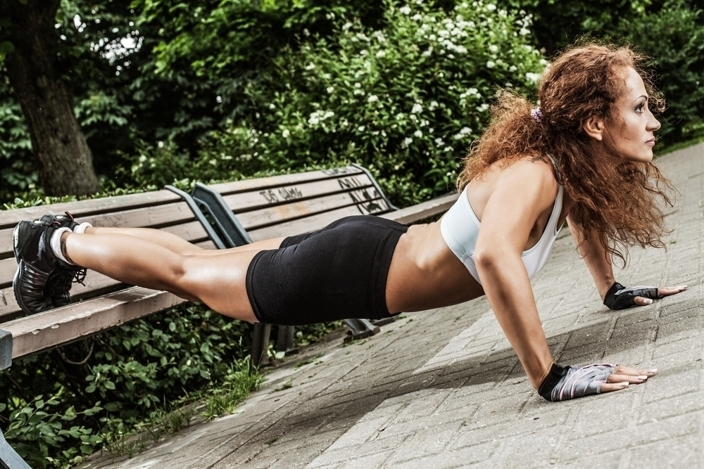Woman performing push-ups on a park bench.