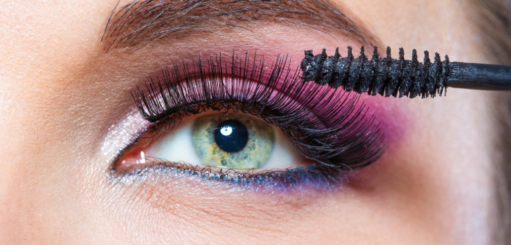 Woman with bright makeup applying mascara.