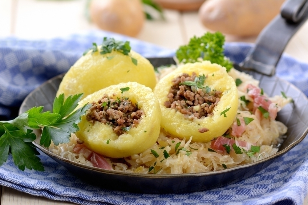Potatoes with a meat dish on a serving plate.