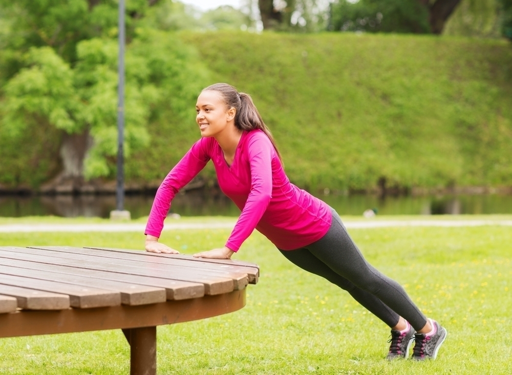 Woman doing mountain climbing exercise on a park bench.