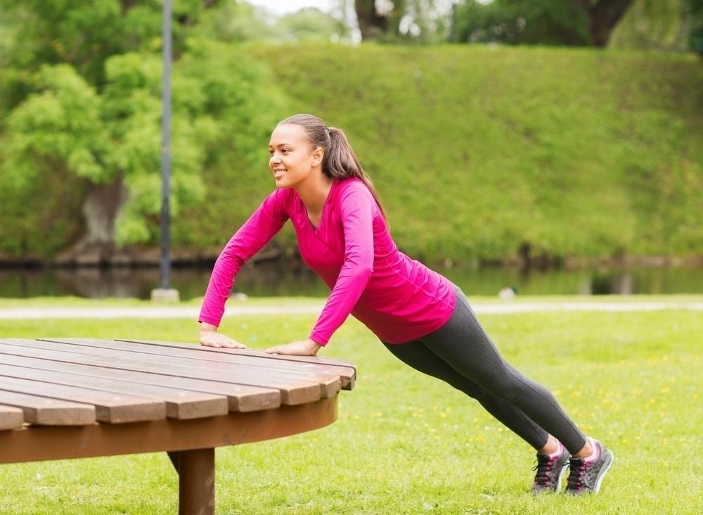 Woman doing mountain climbing exercise on a park bench.