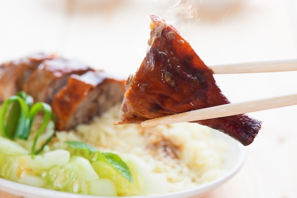 Freshly cooked peking duck dish with chopsticks.