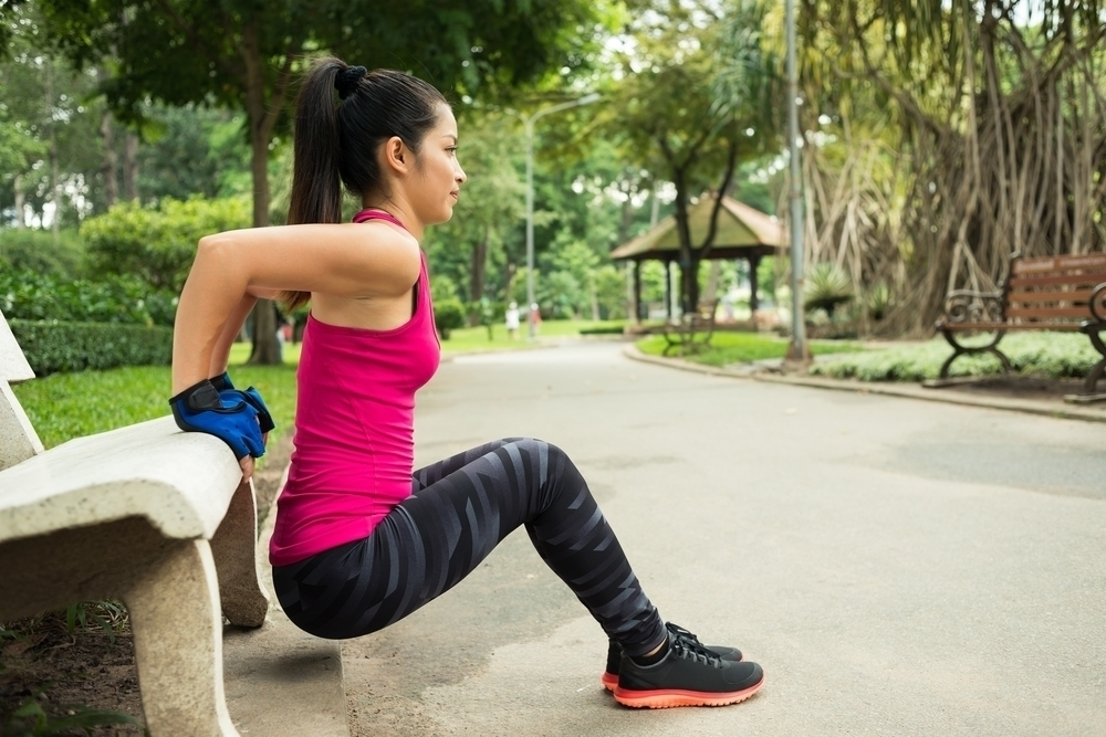 Woman using a park bench for tricep dips.