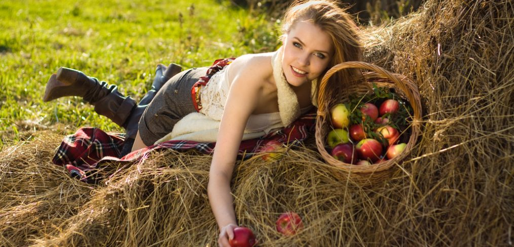 Woman with an apple in hand lying on hay.