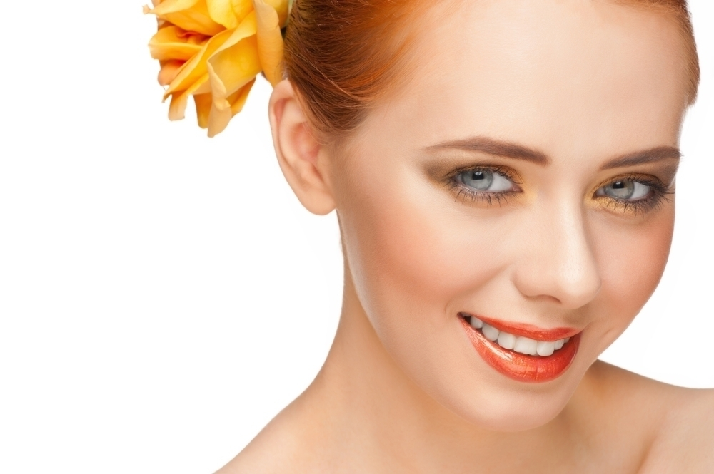 Woman with rose gold eye makeup and a yellow rose on her hair.
