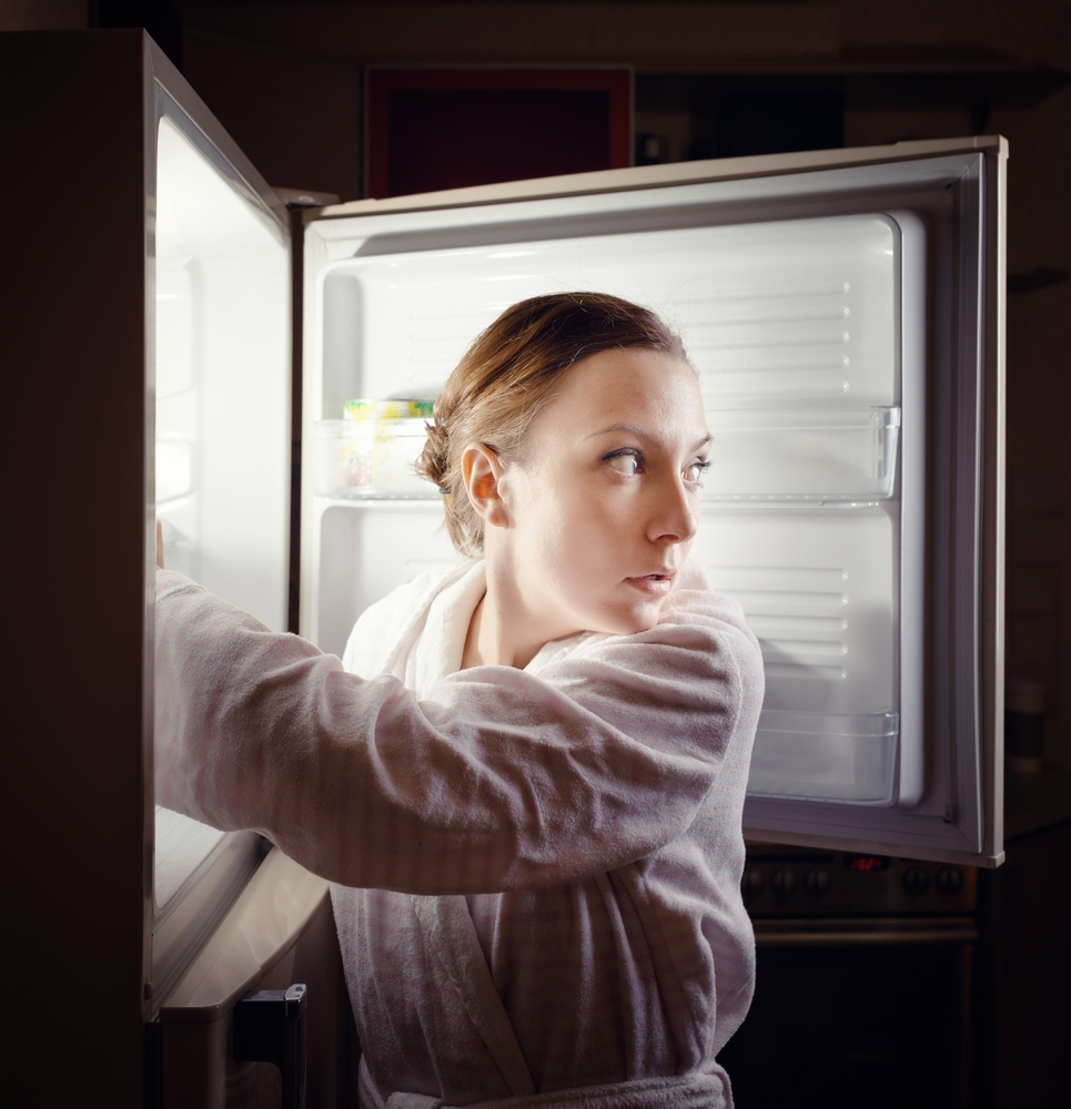 Girl sneaking into the kitchen to eat a midnight snack.