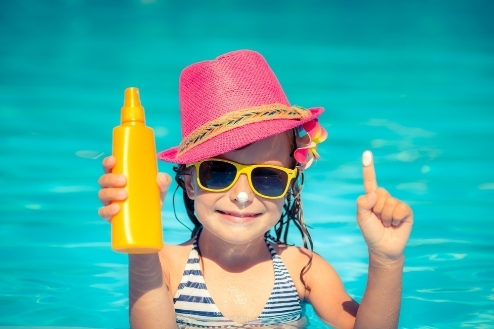 Little girl wearing a hat and sunglasses holding a sunscreen bottle in a beach.
