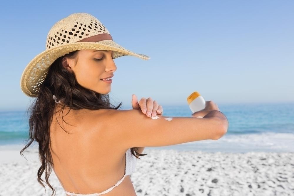 Woman wearing a hat applying sunscreen.