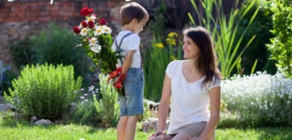 Little boy presenting flowers to mother