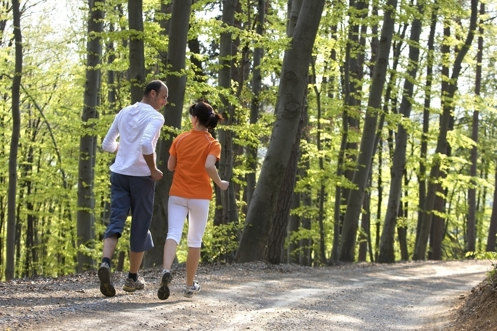 Woman wearing an orange top jogging with her husband in a park.