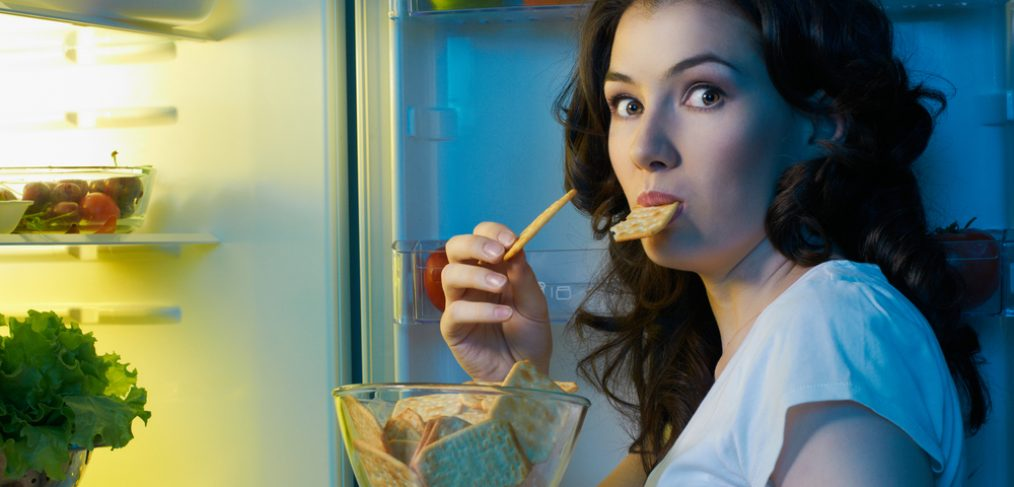 Woman eating a snack at night.