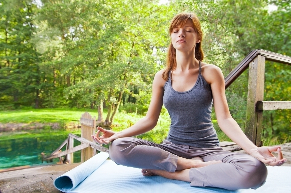 Woman performing a yoga breathing exercise in an outdoor setting.