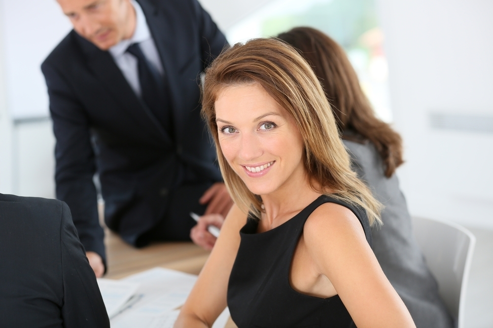 Woman wearing a black dress at a meeting in her office.