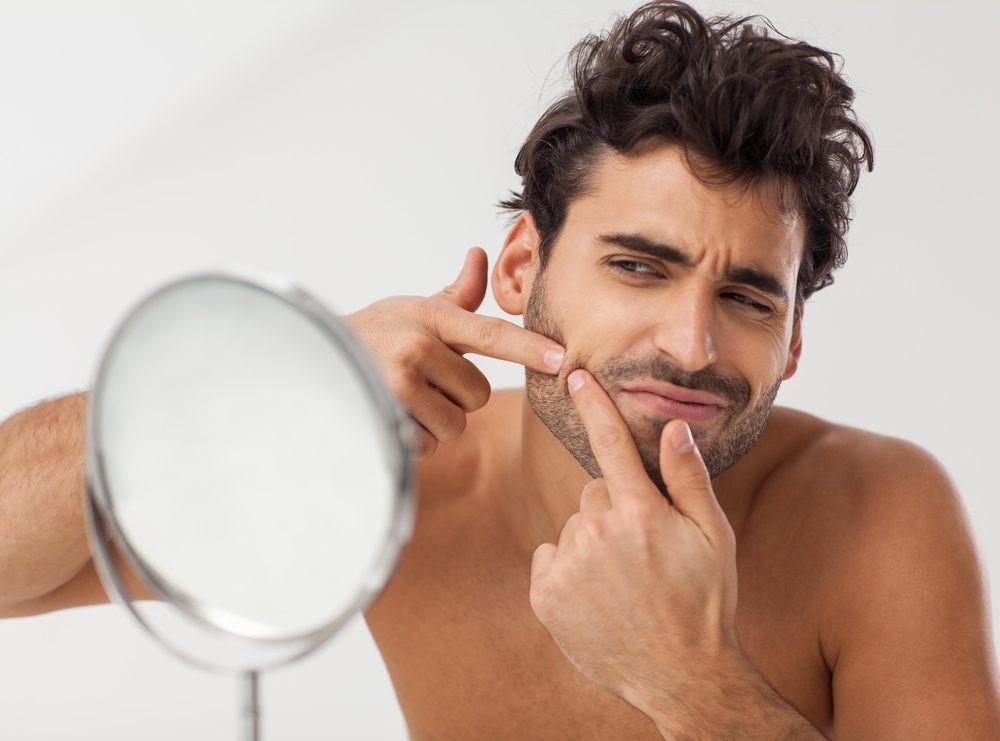 Man examining his pimple in the mirror.