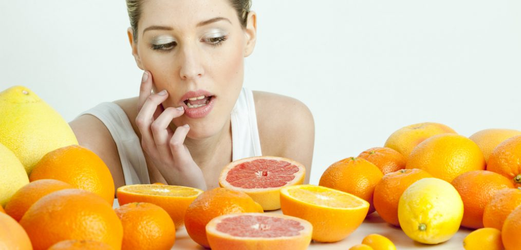 Woman surrounded by citrus fruits deciding what to eat.