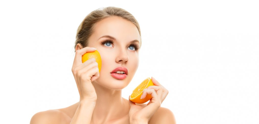 Woman holding an orange close to her face