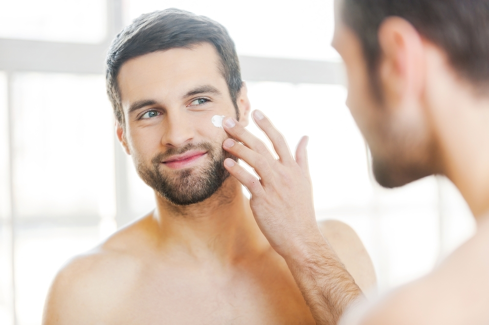 Man applying a moisturizer.