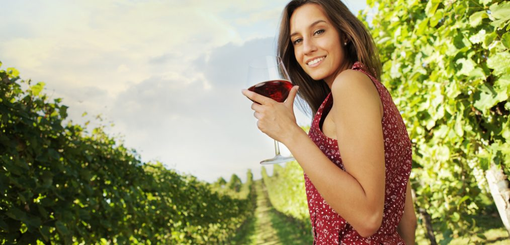 Woman sipping red wine in a vineyard.