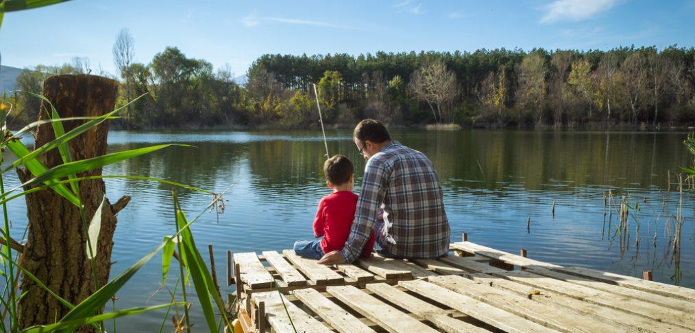 Family sitting beside lake
