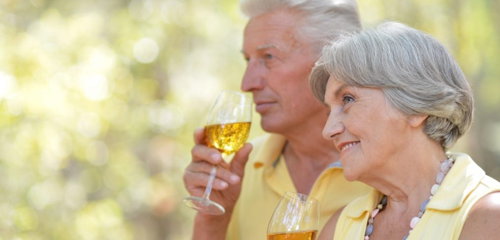 Old couple drinking wine.
