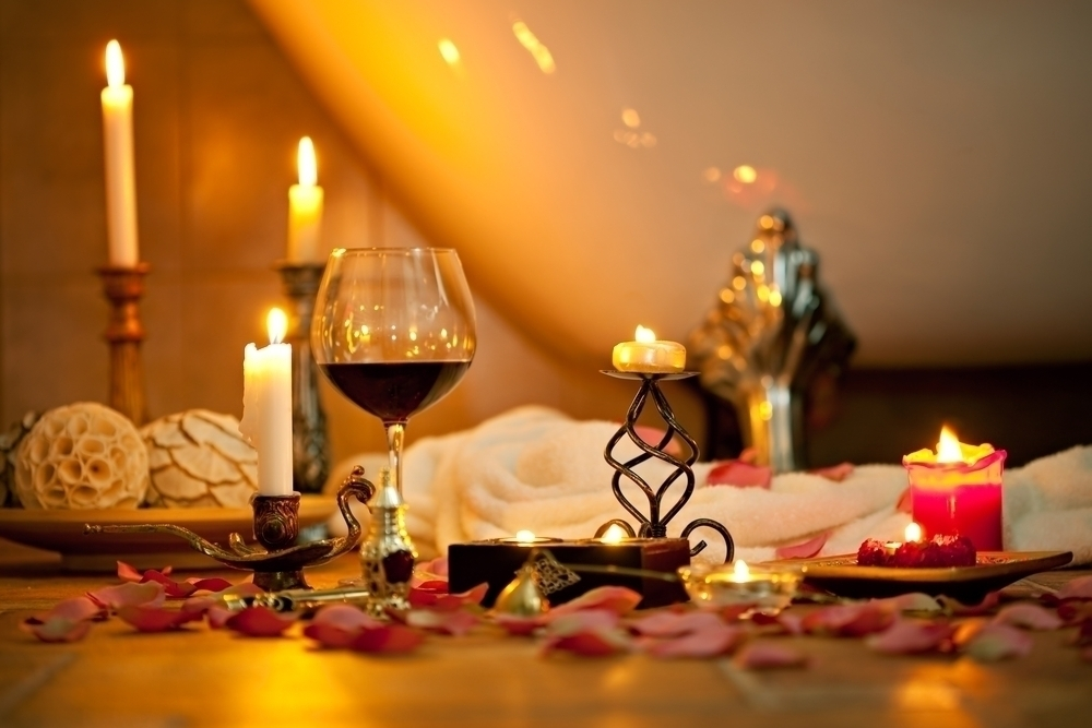 Wine glass and candles next to a bathtub.