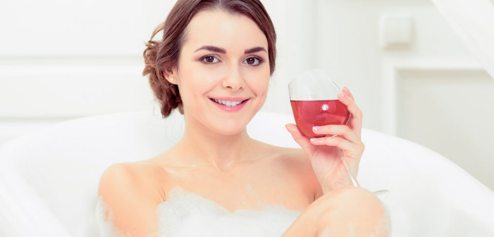 Woman sipping wine while taking a bath