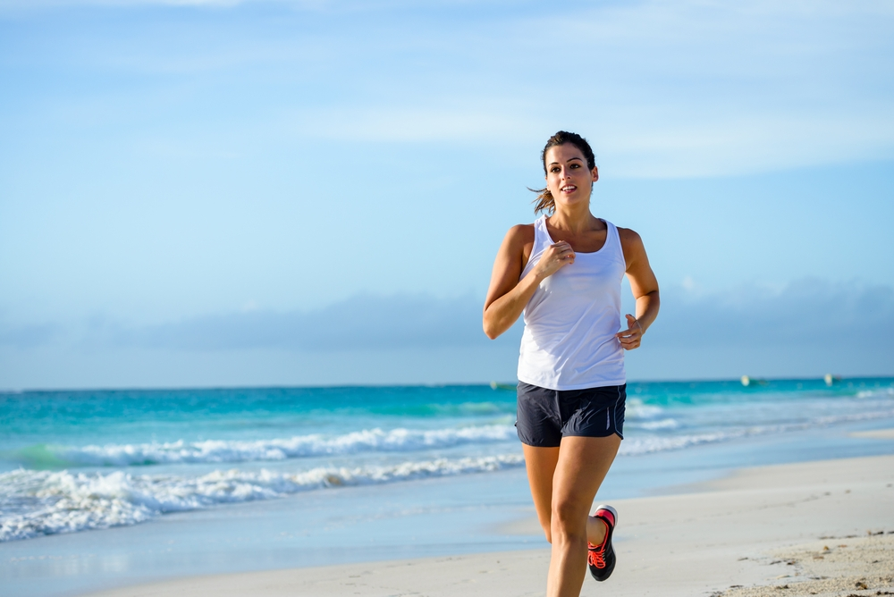 Woman jogging in a beach.