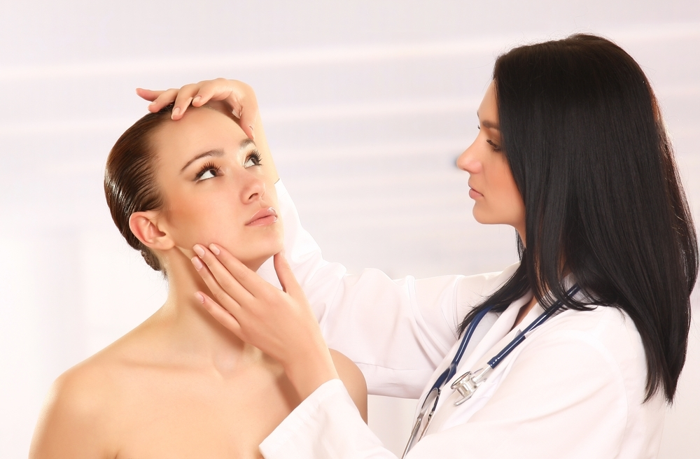 Dermatologist examining a woman's face.