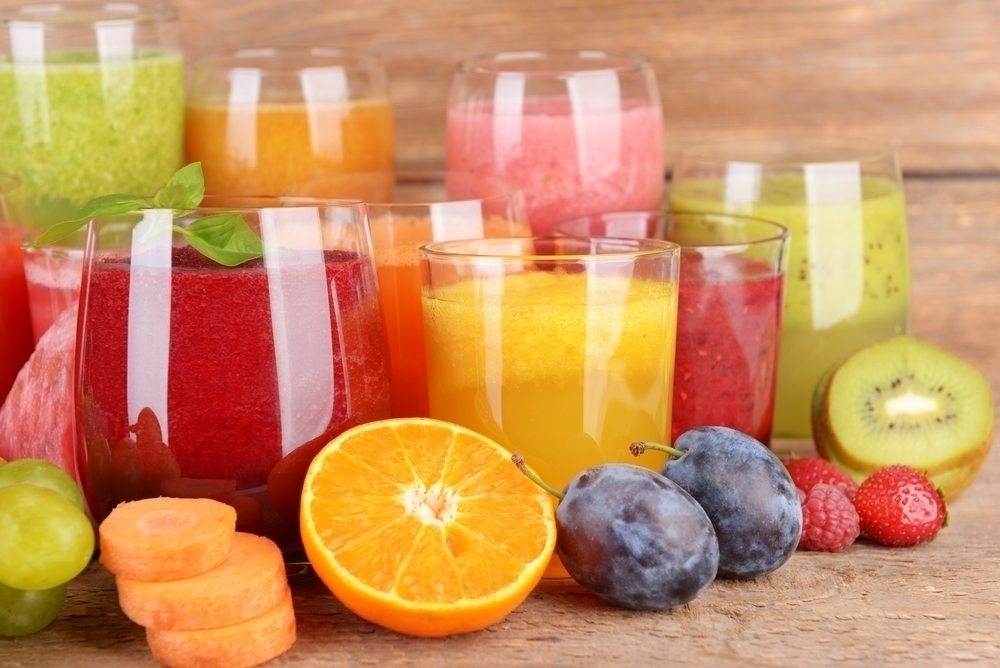 Different types of juices on a wooden table.