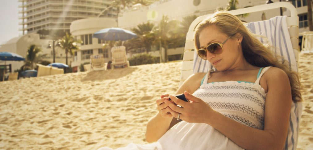 Woman looking at her phone in a beach.