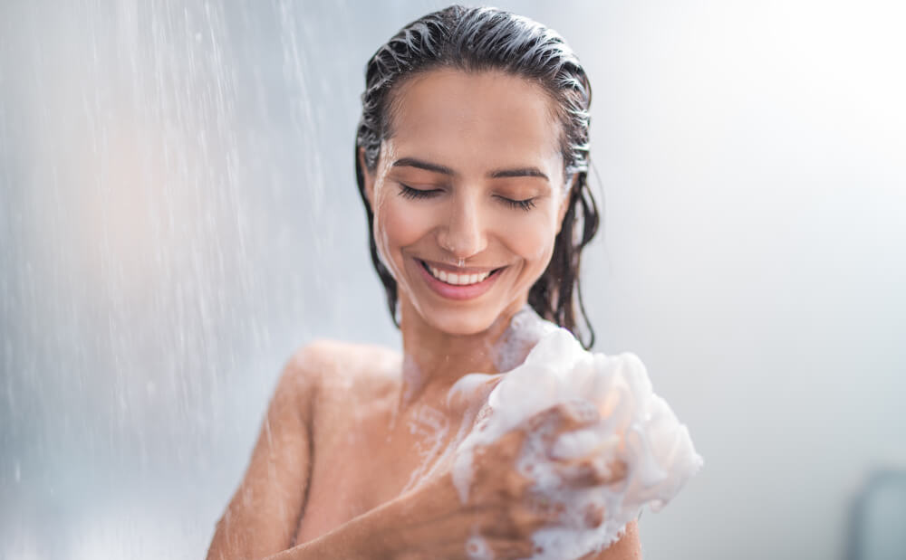 Young smiling woman taking a shower and using a luffa