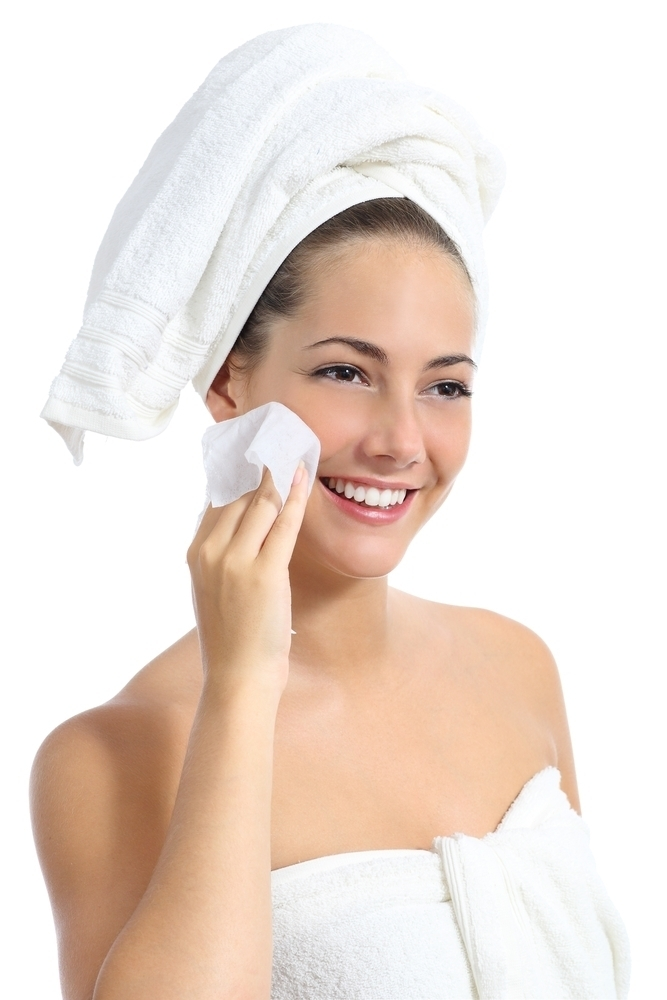Woman cleansing her face with a wipe.