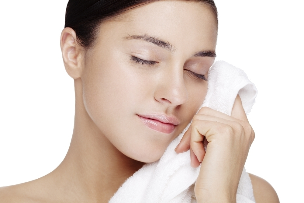 Woman wiping face with a towel.