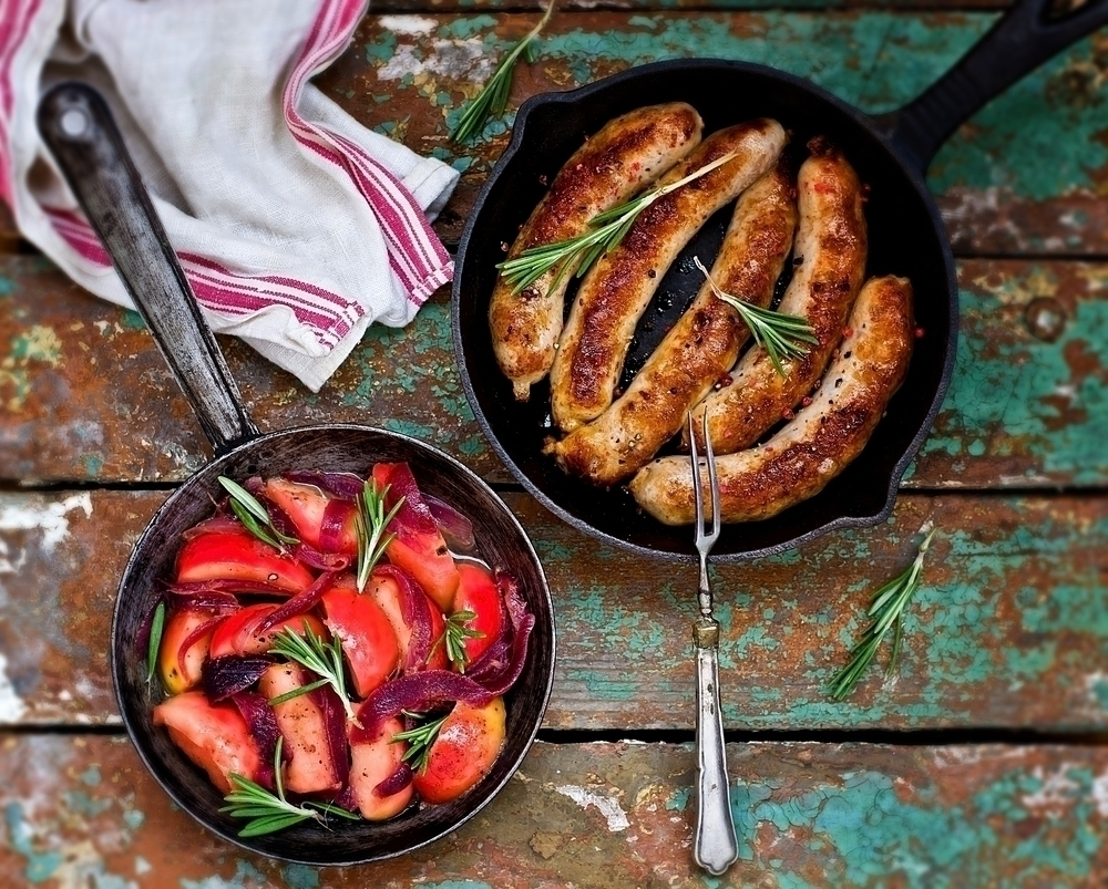 Freshly cooked sausages and tomato dish, still in pan