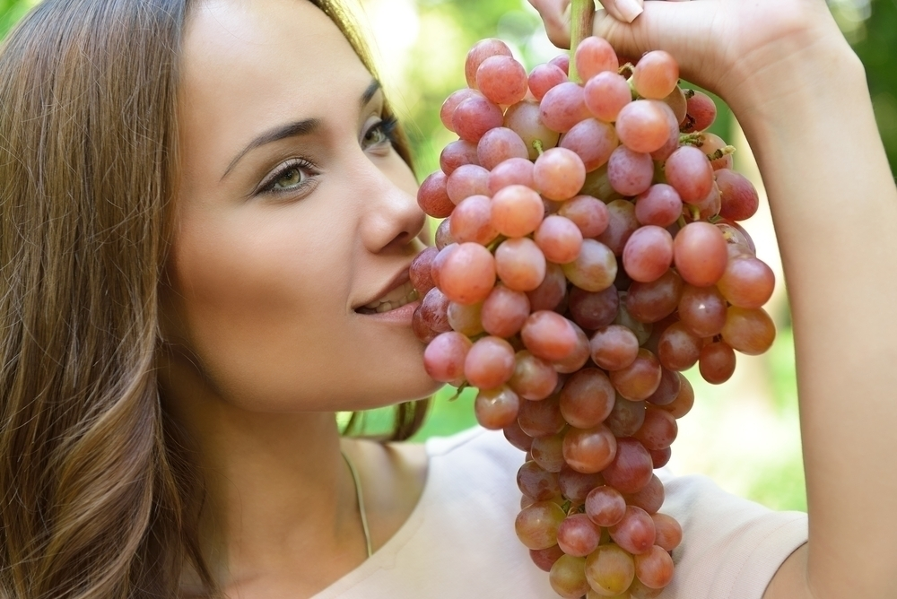 Woman holding a bunch of grapes.